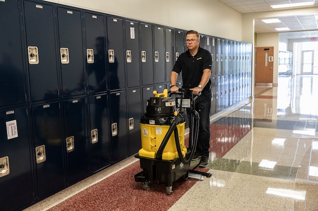 Custodial worker using an autovac. Courtesy of Kaivac.